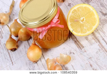 Fresh organic honey in glass jar onions and lemon on old wooden background healthy nutrition strengthening immunity and treatment of flu poster