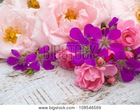 Pale pink and small bright pink roses and geranium bouquet on the white rough wooden table poster