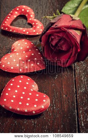 red rose and three heart shape on wood background.