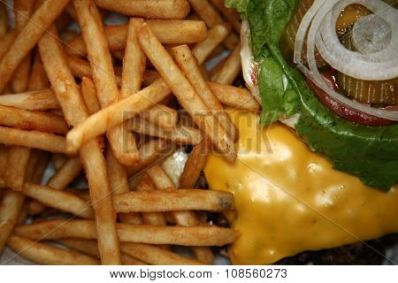 French Fries and Cheese Burger in a restaurant. Shot at a shallow depth of field focus on the French fries .