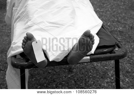 Gruesome image of a dead persons feet with a toe tag to identify the person and cause of death, next of kin and any other important information.