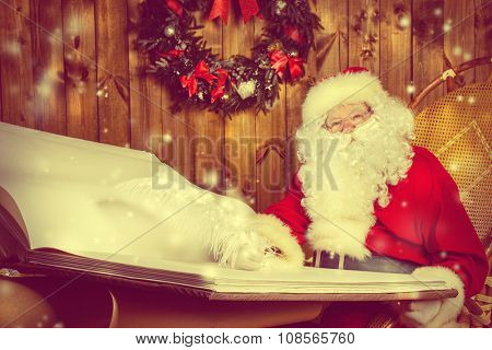 Santa Claus writing a magic book in his wooden house. The magic of Christmas.
