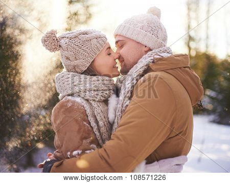 Young amorous couple in winterwear going to kiss