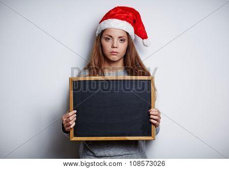 Sulky girl in Santa cap showing empty blackboard