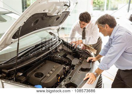 Businessman explaining the car details at new car showroom