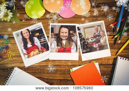 Snowflakes against overhead view of office supplies with blank instant photos