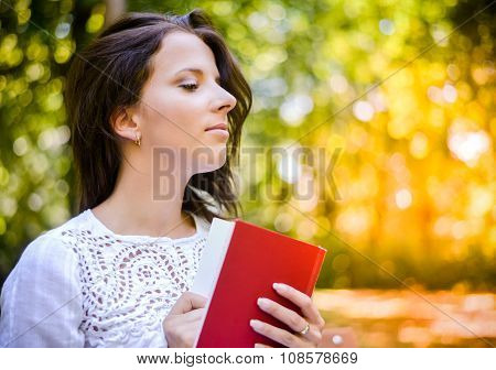 Thoughtful Woman Holding A Book At The Park
