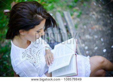 Intellectual Woman Reading A Book In The Park