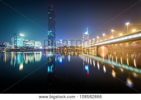Donau City And The Danube River At Night, Seen From Donauinsel, In Vienna, Austria.