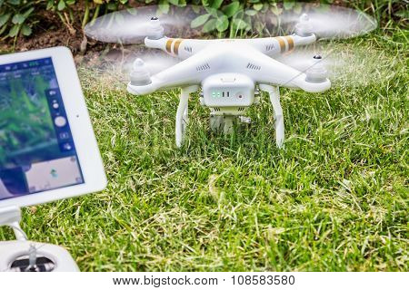 FORT COLLINS, CO, USA - AUGUST 28, 2015:  DJI Phantom 3 quadcopter drone with a radio controller and iPad Air tablet ready to take off from a backyard lawn.
