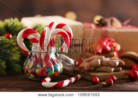 Christmas Candy Canes in jar with Christmas decoration on table on bright background