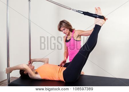 Pilates aerobic instructor woman with in cadillac fitness exercise