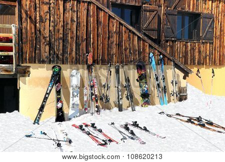 Skis and snowboards on the snow and against alpine chalet
