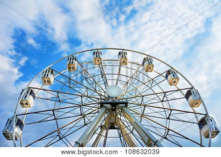 Ferris wheel with numbered cabins - business motivation. Bright blue sky with sharp clouds behind it. poster