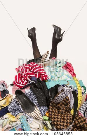 Woman Legs Reaching Out From A Big Pile Of Clothes And Accessories.