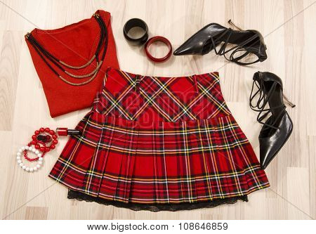 Winter Sweater And Plaid Skirt With Accessories Arranged On The Floor.