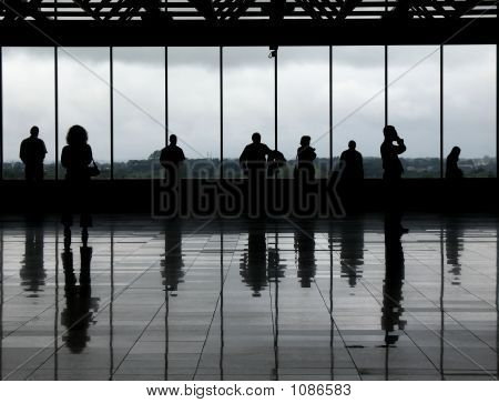 silhouetted people against the windows of an airport observation deck. the greyish floor and clouded day gives it a very monochrome aspect. poster