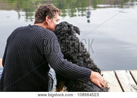 Man Snuggles Dog At Lake