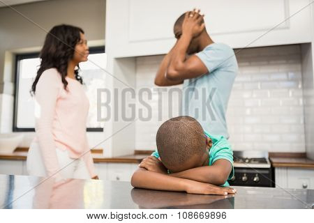 Mother and father arguing in the kitchen around their son
