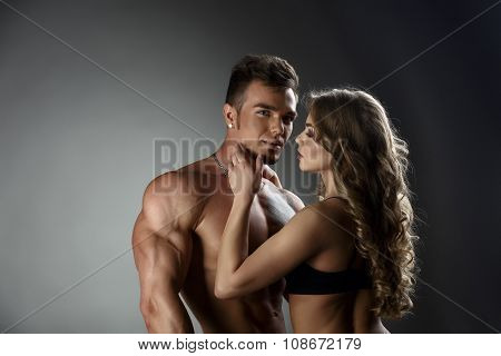 Loving woman admires sexy tanned bodybuilder
