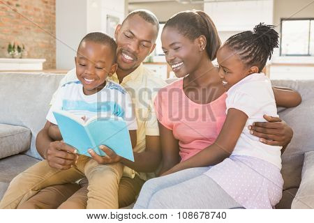 Happy family reading a book together in living room