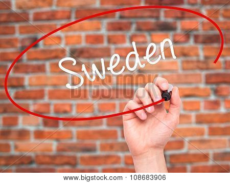 Man Hand writing Sweden with black marker on visual screen.