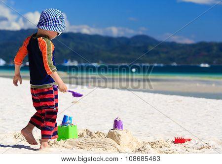 child building sandcastle