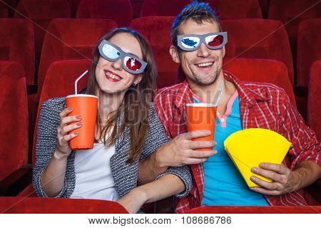 The spectators sitting in the cinema and watching movie  with cups of cola and popcorn. Concept of a variety of human emotions. poster