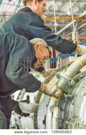 Workers install aviation engine. Tyumen. Russia