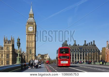 LONDON UK - APRIL 12 2015: double-decker bus passes pedestrians walking in front of Big Ben and Houses of Parliament on Westminster Bridge.