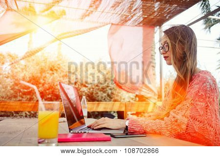 young successful female freelancer using net-book for distance work during morning breakfast