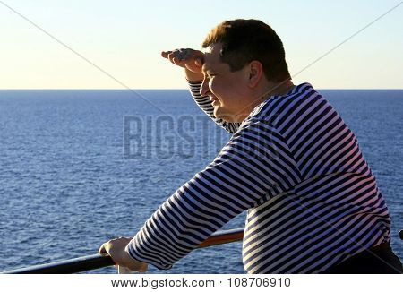 STENA, POLAND - 28 April 2007: A man in a vest looks into the distance holding the palm canopy near the forehead