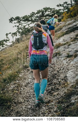 group of young women athletes climb mountain one after another