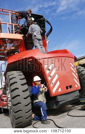 giant fork truck being serviced by three mechanics