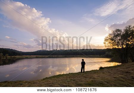 Child Looking At Bright Sunset Over Lake