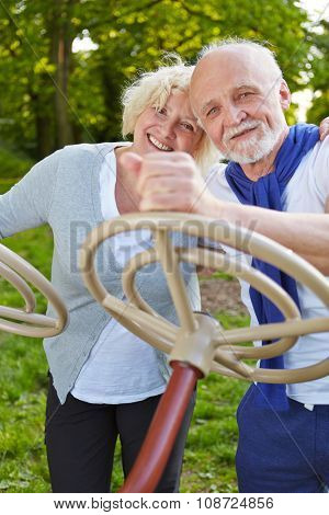 Two happy senior people playing with a steering wheel in a park in summer