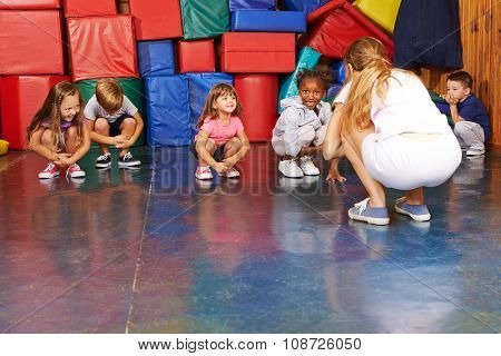 Children doing gymnastics in physical education with nursery teacher in preschool