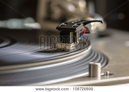 Close up of a turntable needle head playing music from an lp