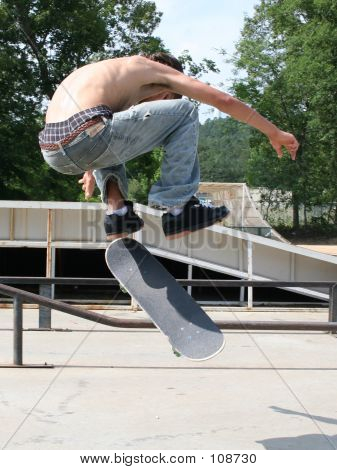 Teen boy shirtless in jeans skateboarding at outdoor skatepark. poster