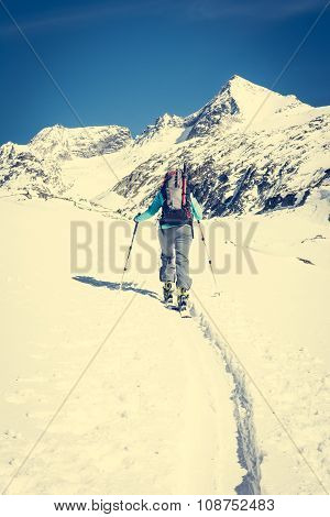 Ski touring in sunny weather. Female skier ascending a trail. poster