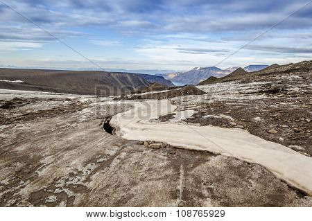 Frozen River Meanders In The Middle Of The Glacier In The Mountains