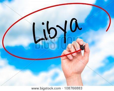 Man Hand writing Libya with black marker on visual screen.