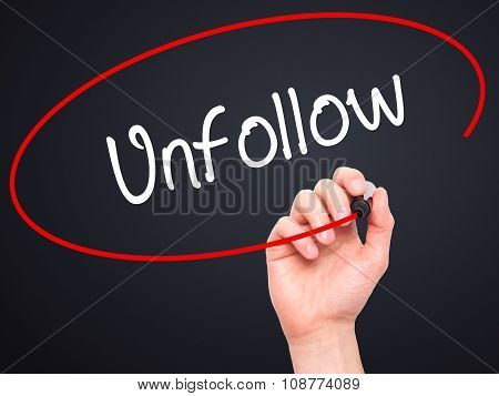Man Hand writing Unfollow with black marker on visual screen.