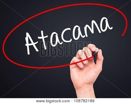 Man Hand writing Atacama with black marker on visual screen.