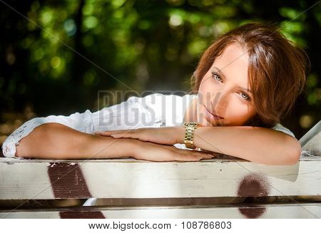 Pretty Woman Leaning On A Bench At The Park