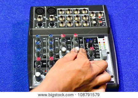 Hand audio mixing console on blue background. poster