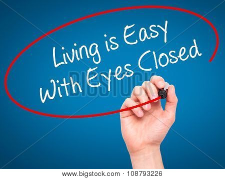 Man Hand writing Living is Easy With Eyes Closed with black marker on visual screen