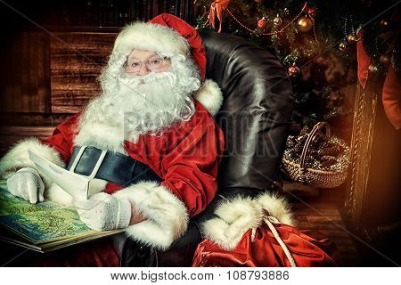Santa Claus reading letters from children and looking at the world map. He is at home, decorated for Christmas. Santa's mail.