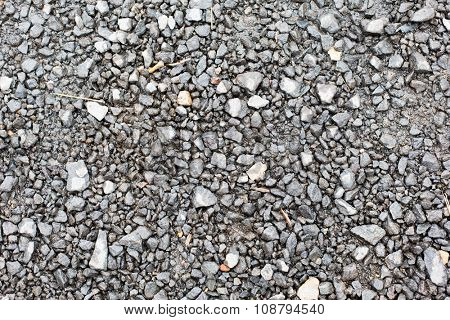 background and texture concept - close up of gray macadam stones on ground