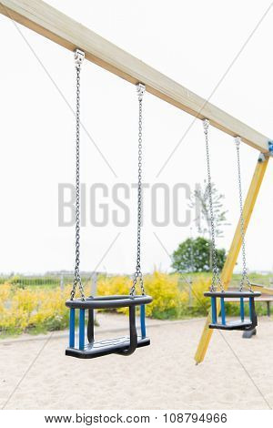 childhood, equipment and object concept - baby swing on playground outdoors poster